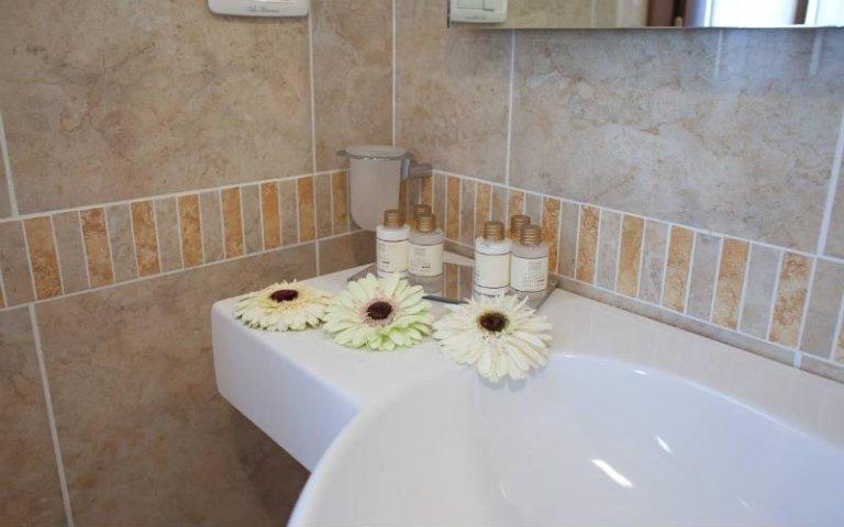 dei fiori e dei saponi vicino a un lavabo