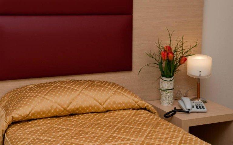 un letto singolo e accanto un comodino con un telefono e una lampada