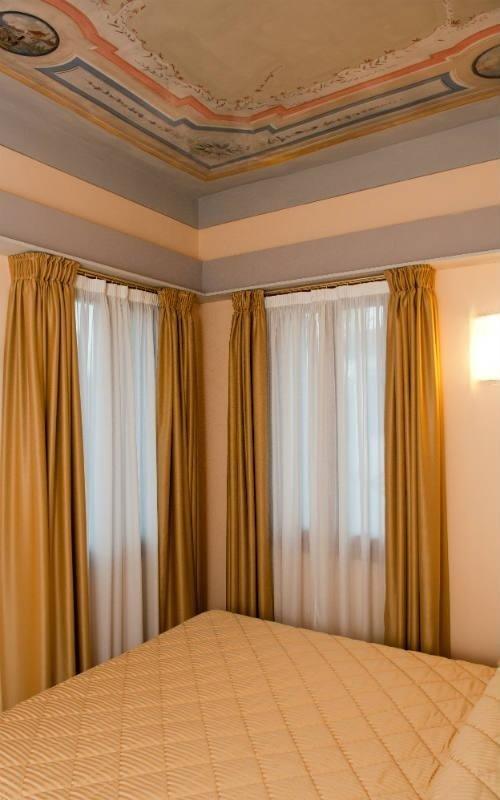 due finestre con tende dorate e bianche