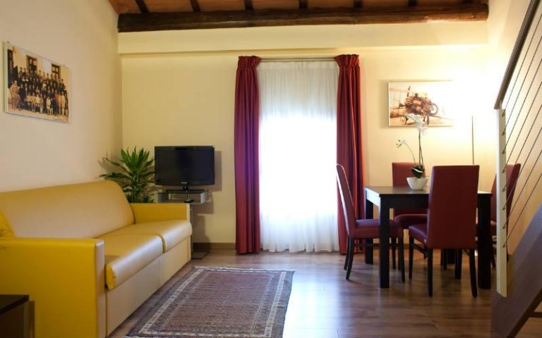 una sala con un divano giallo,un tavolo con delle sedie e una finestra con tende bianche e rosse