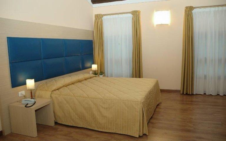 un letto matrimoniale con 2 comodini con delle lampade  accese