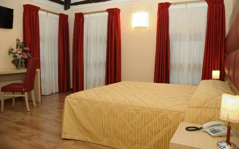 un letto matrimoniale in una stanza d'hotel con tende bianche e rosse