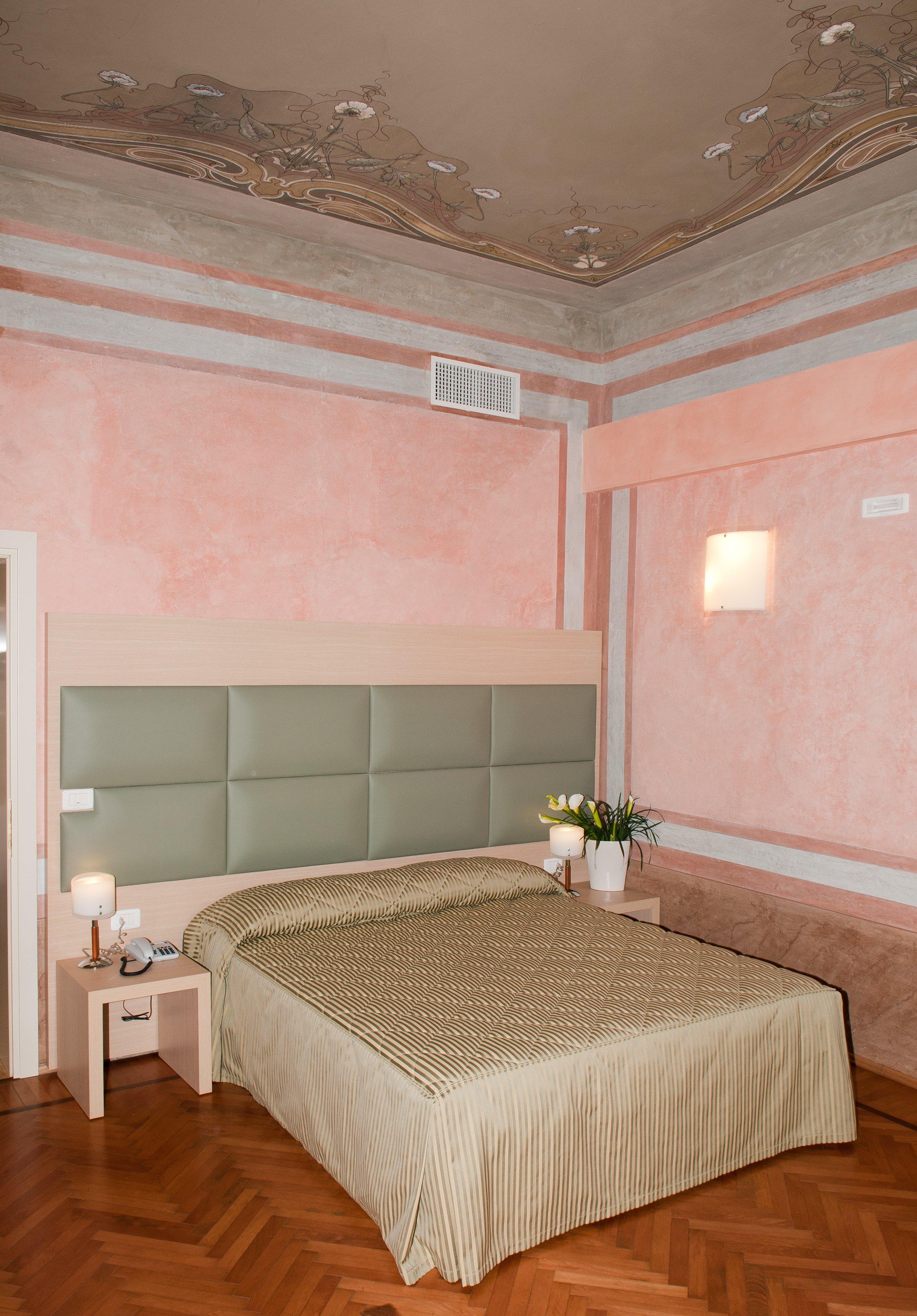 una stanza d'albergo con letto matrimoniale e pareti rosa