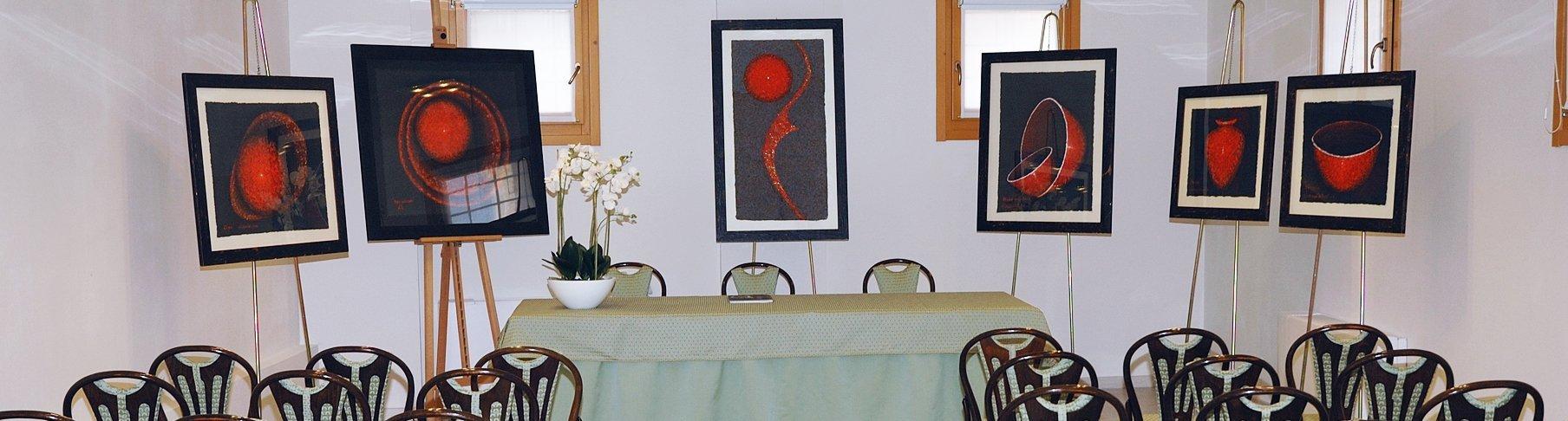 una stanza con delle sedie e dei quadri esposti