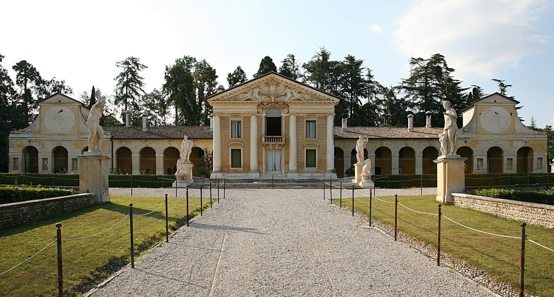 veduta frontale di un palazzo antico con statue e archi