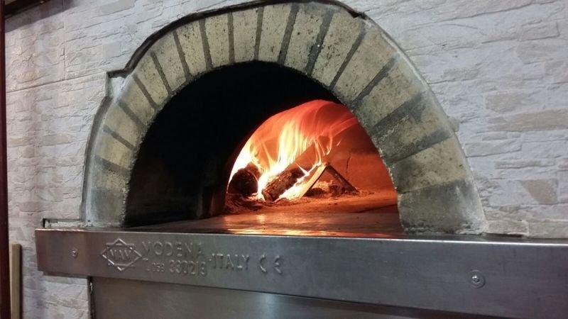 Vista di un forno in legno acceso con scritto Modena, Italy davanti