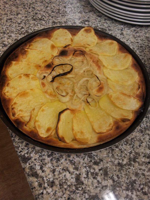 Un tagliere di una pizza bianca con patate e cipolle