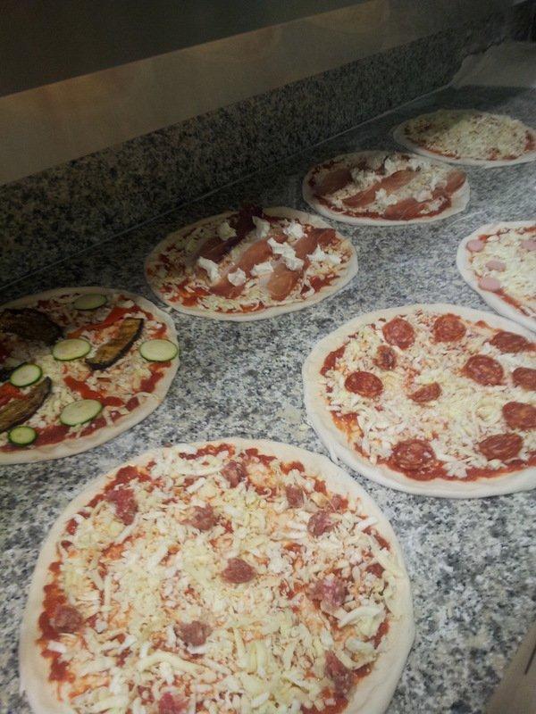 Insieme di vari tipi di pizze pronti per essere infornati  appoggiati sul piano
