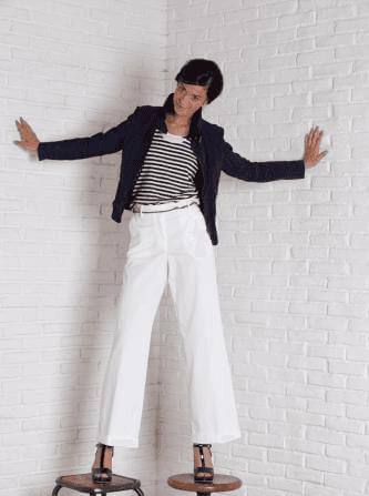 modella indossa maglietta a righe con giacca blù e pantaloni bianchi a vita alta seventy