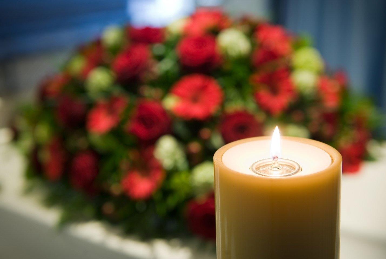 cero e fiori rossi su una bara, sullo sfondo