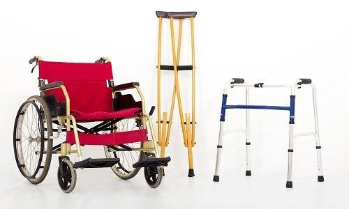 una sedia a rotelle dei ,bastoni canadesi e un deambulatore