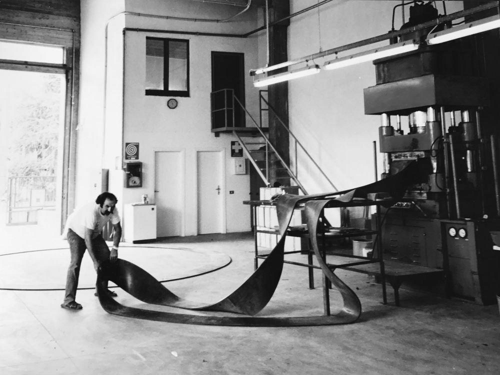 foto in bianco e nero di un uomo in una fabbrica con in mano  della gomma per guarnizioni