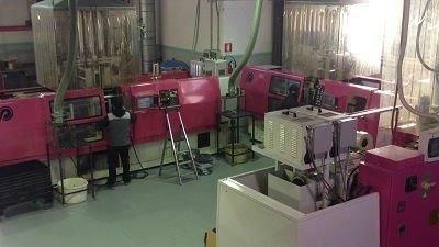interno di una fabbrica con un uomo vicino a dei macchinari viola