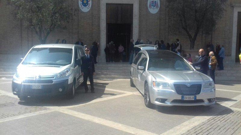 carro funebre e furgone parcheggiati fuori dalla chiesa