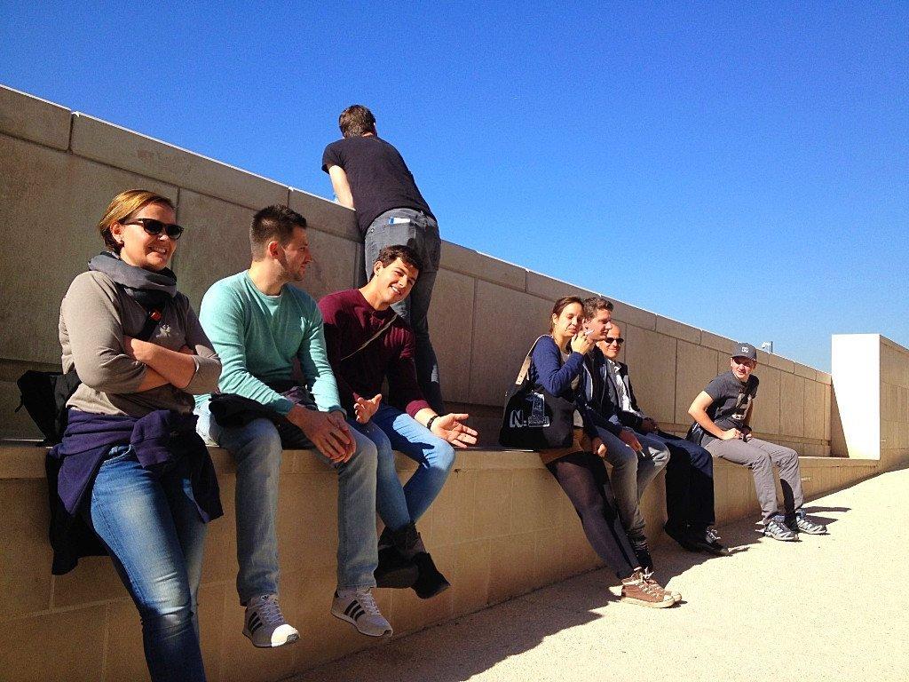 Eine Gruppe von Menschen auf dem weiten Dach der Friche la Belle de Mai in Marseille, die auf die Kamera zukommen.
