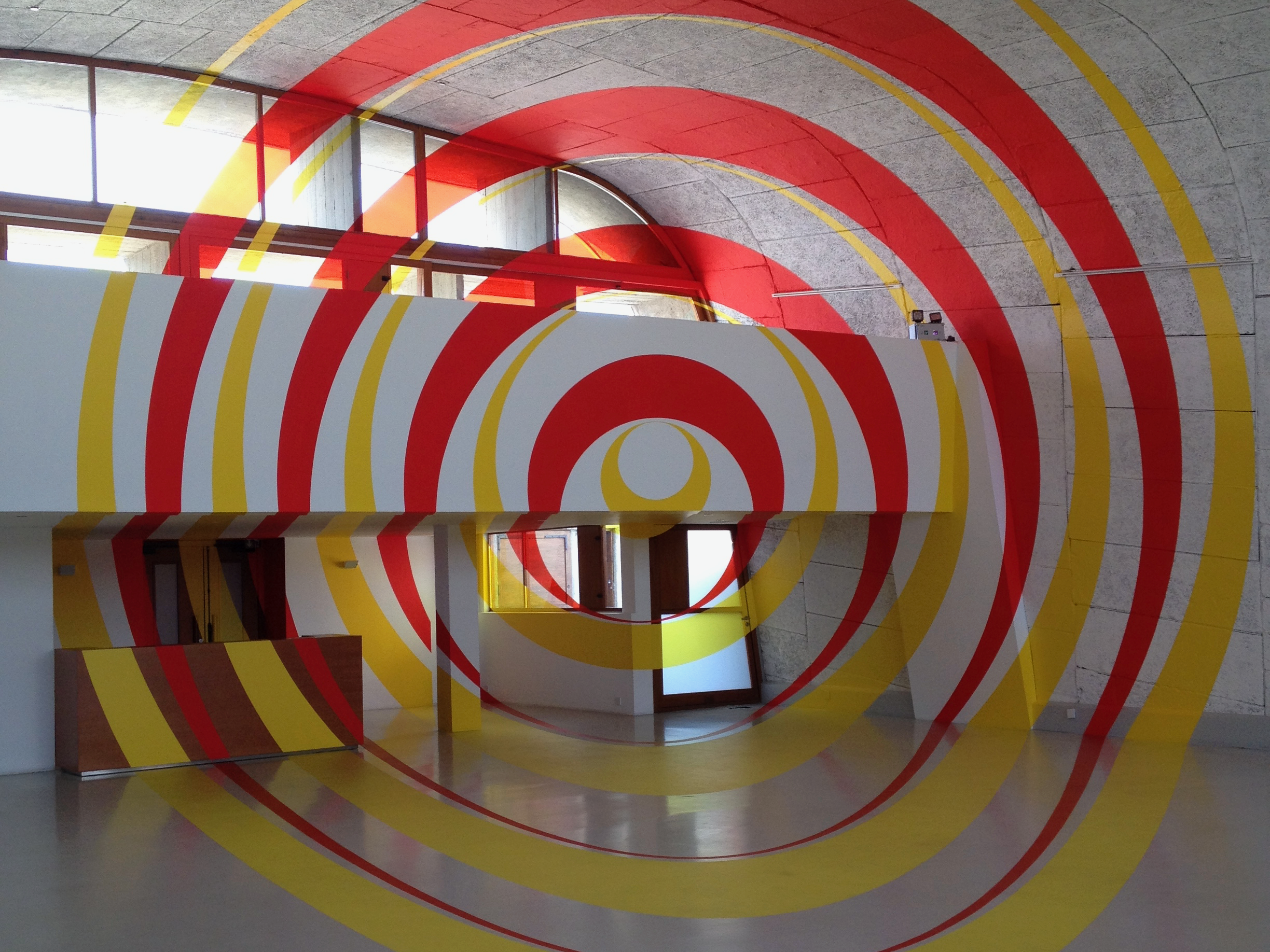 A red and yellow circle inside a room showing an artwork of Felice Varini in the MAMO, Marseille Modulor on the roof of the Cité Radieuse in Marseille.