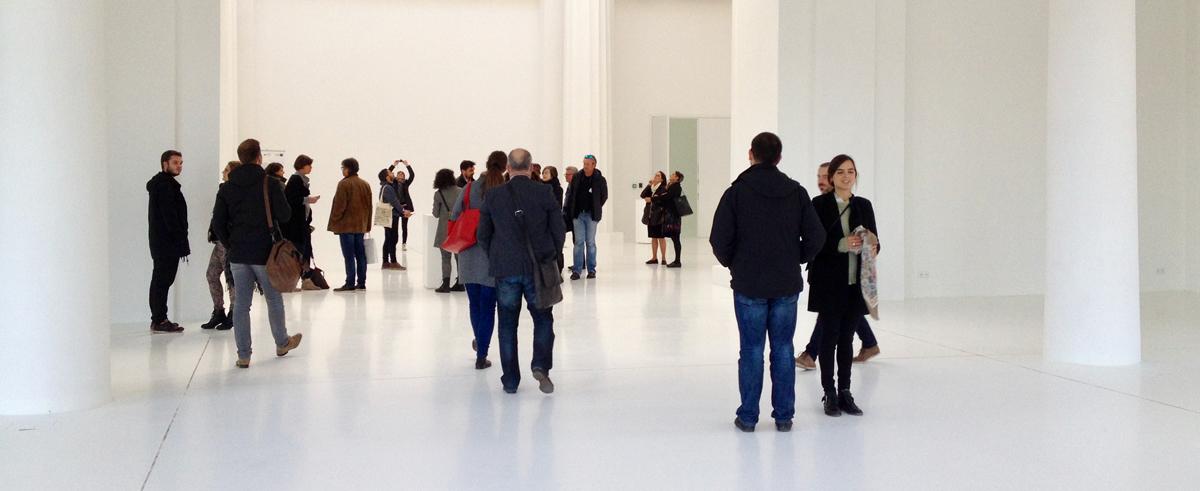 Eine Gruppe von Besuchern in einem weissen Raum eines Museums, die sich umsehen.