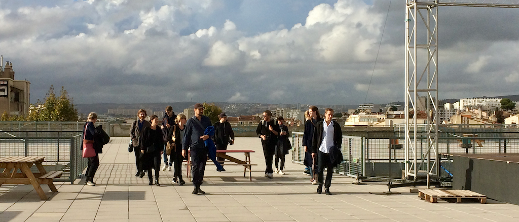 A group of people on the rooftop of the Friche la belle de Mai walking towards the camera.