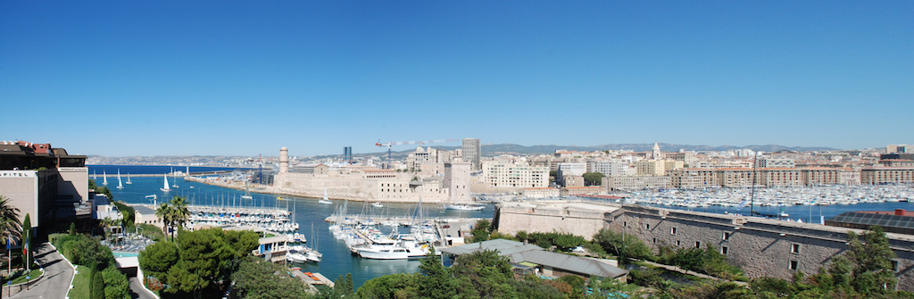 View on the harbour of Marseille, overlooking the new museums and the old town Panier on blue sky.