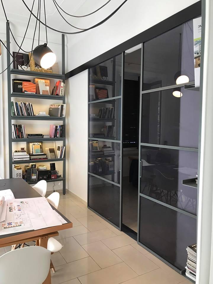 una porta a due ante in vetro e vista di uno scaffale in ferro