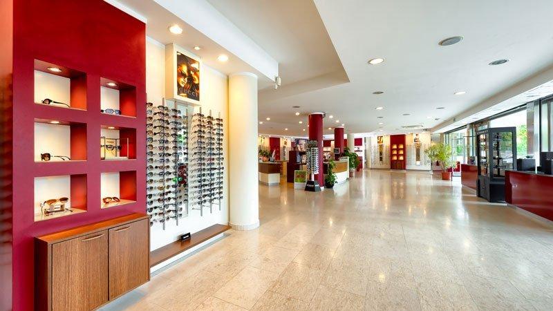 interno di un negozio molto ampio con sulla sinistra degli occhiali esposti su delle mensole e su un pannello di color rosso e in lontananza altre esposizioni in vetrine