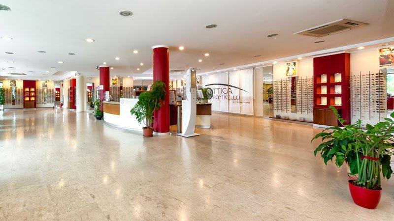 interno dell,Ottica Ponticello con delle colonne rosse dei vasi con delle piante, occhiali esposti su dei pannelli