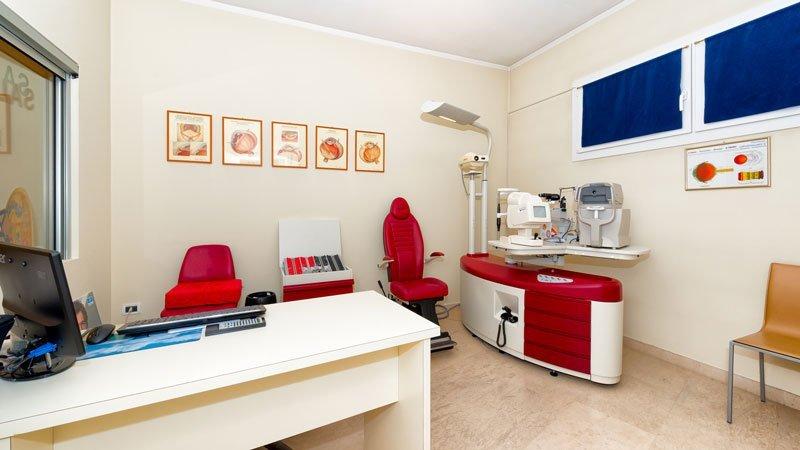 un ufficio con una scrivania  bianca con sopra un monitor, due sedie rosse e sulla destra dell' apparecchiatura per test della vista