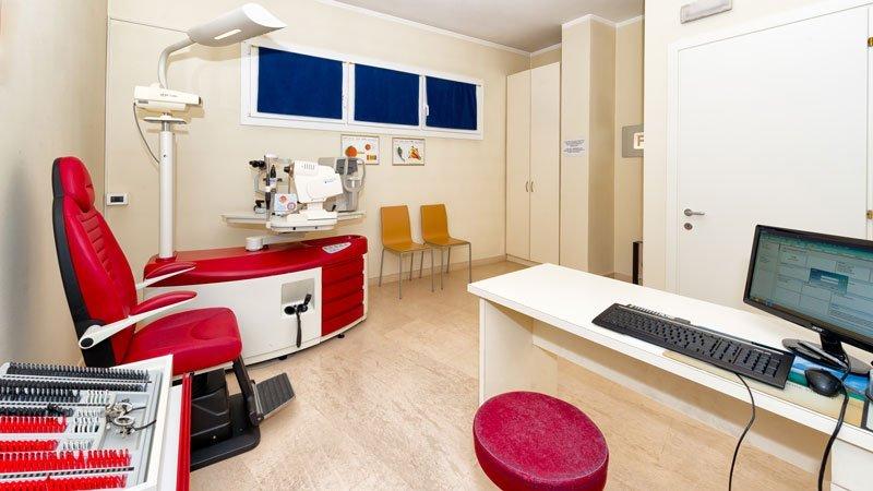 vista dell ufficio da dietro la scrivania con monitor acceso , uno sgabello rosso, una poltrona di pelle rossa e un macchinario per test ottici