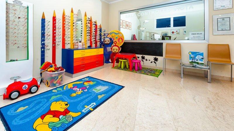 vista di una saletta d'attesa con un tappeto di Winnie the Pooh una macchinina grande dei pupazzi dei Teletubbies una cassettiera di diversi colori e delle matite colorate disegnate sulla parete