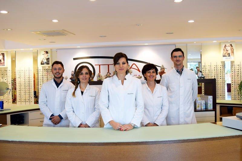 degli uomini e delle donne con un camice bianco sorridenti dietro a un bancone all'interno dell'ottica