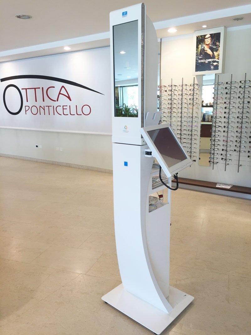 un pannello bianco con un monitor, dietro la scritta ottica Ponticello sul muro e degli occhiali da vista esposti