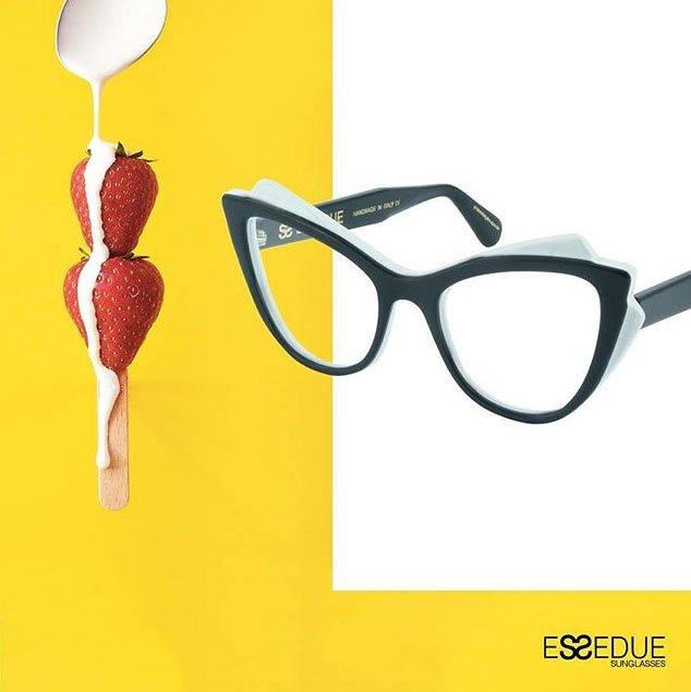 un'immagine su uno sfondo bianco e giallo raffigurante un paio di occhiali da vista neri, sulla destra un cucchiaio da cui cola della crema che si riversa su delle fragole infilate in un bastoncino di legno