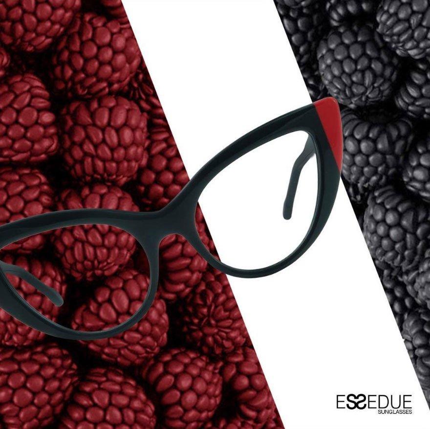 un'immagine di un paio di occhiali da vista neri con un lato bordeaux su uno sfondo con dei lamponi e delle more