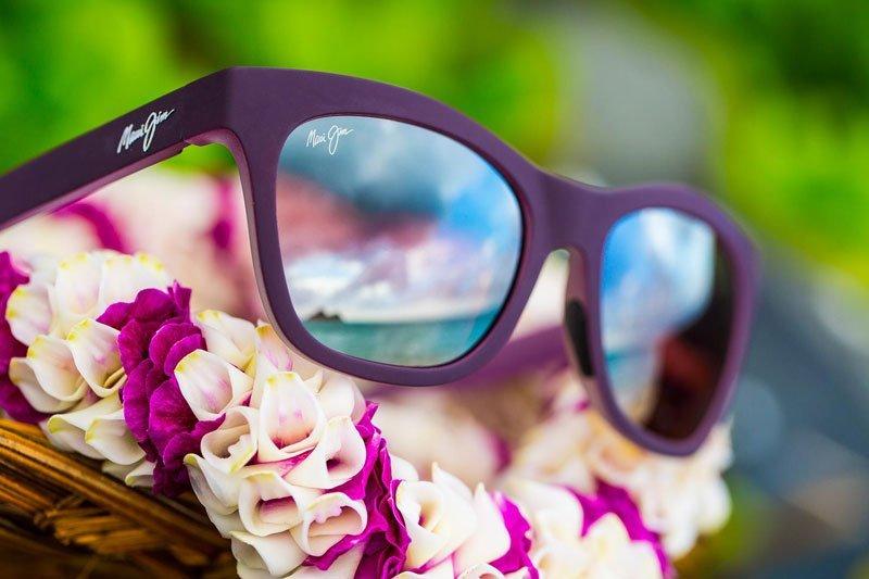 un paio di occhiali da vista di color viola sotto dei fiori bianchi e viola e dietro uno sfondo verde