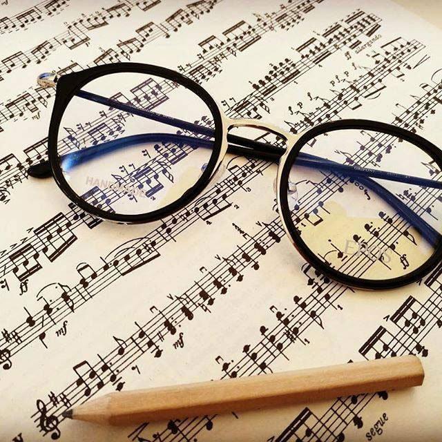 degli occhiali da vista neri e accanto una matita entrambi appoggiati su uno spartito musicale
