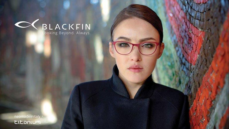 una donna con un cappotto nero a doppiopetto che indossa degli occhiali da vista rossi e sulla sinistra la scritta Blackfin looking Beyond Always