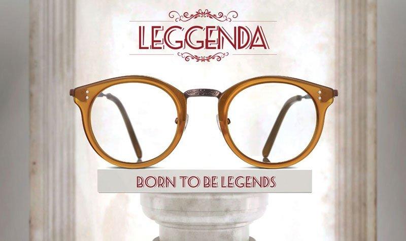 un paio di occhiali da vista gialli, sopra la scritta Leggenda di color rosso e sotto un'altra con scritto Born To Legends appoggiata su una colonna di marmo