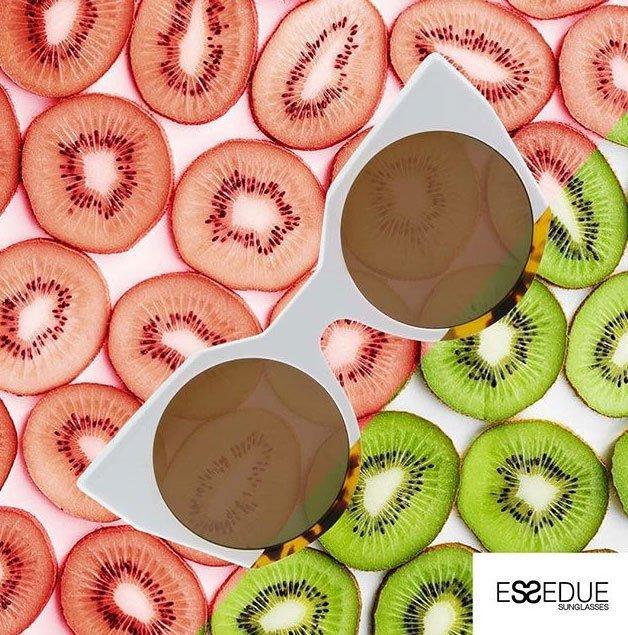 occhiali da sole bianchi con lenti rotonde beige su uno sfondo di fette di kiwi rossi e verdi