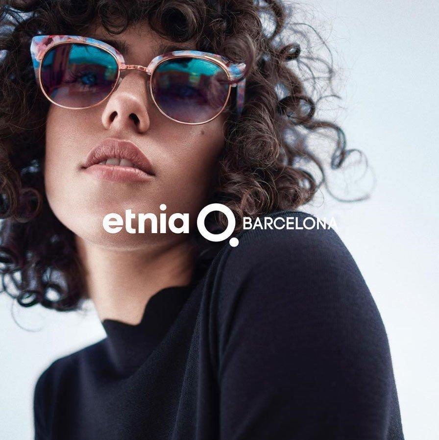 una donna con capelli ricci neri che indossa un paio di occhiali da sole blu e rosa e sotto la scritta Etnia Barcelona