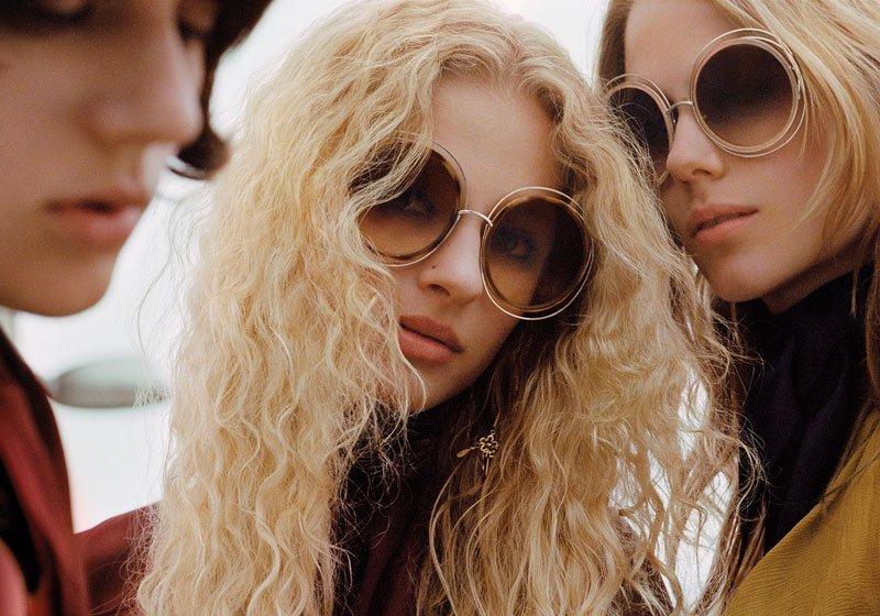 immagine di tre donne,sulla sinistra una con capelli castani, in mezzo una bionda con capelli ricci che indossa degli occhiali da sole rotondi di color beige con lenti marroni e sulla destra un'altra bionda con capelli corti che indossa gli stessi occhiali