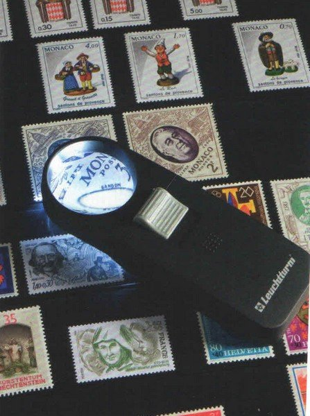 una torcia con una lente d'ingrandimento e dei francobolli
