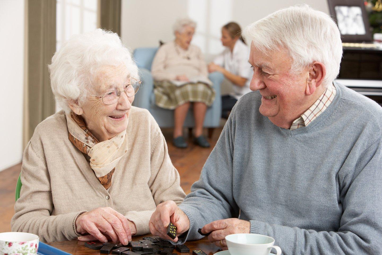 due persone anziane chiaccherano e giocano a dadi