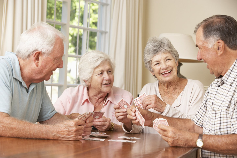 anziani che sorridono mentre giocano a carte