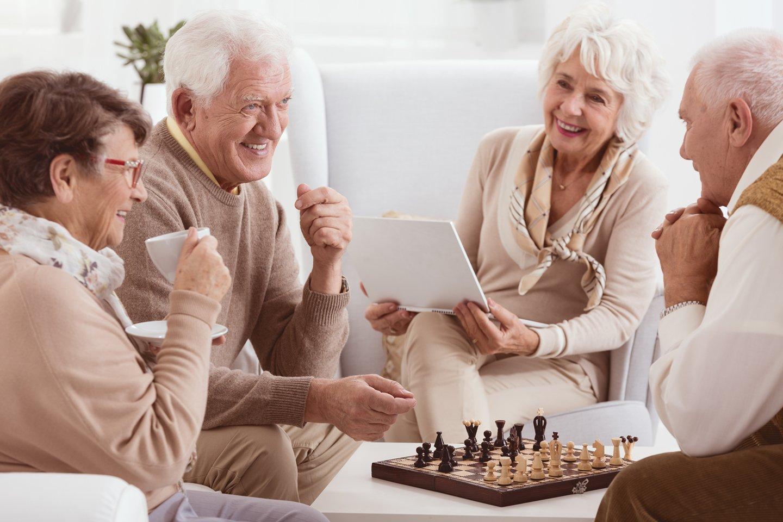 anziani che sorridono mentre giocano a scacchi