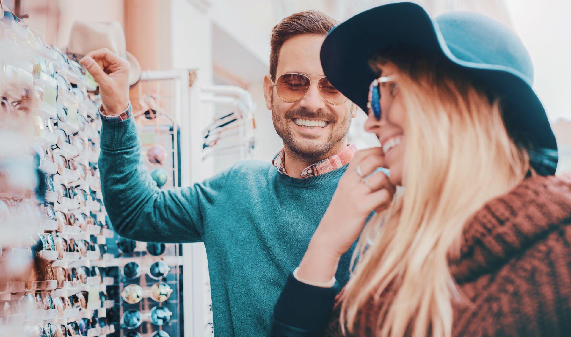 Un coppia di giovani durante la scelta di occhiali da sole