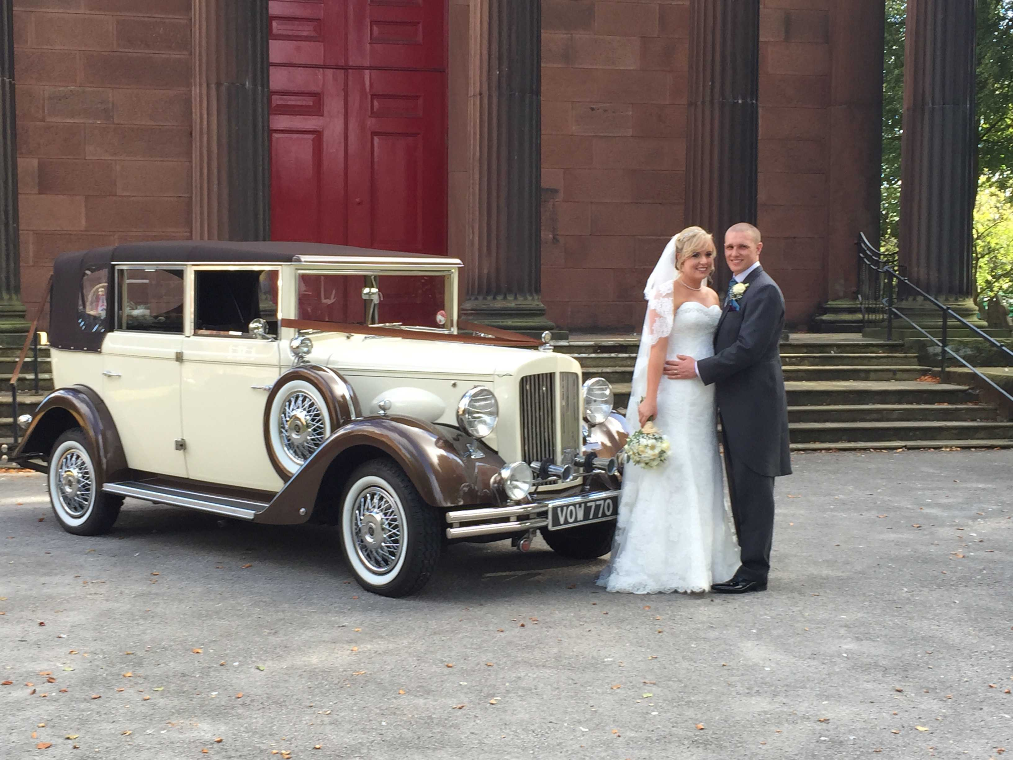 Bride and groom in front of a vintage car