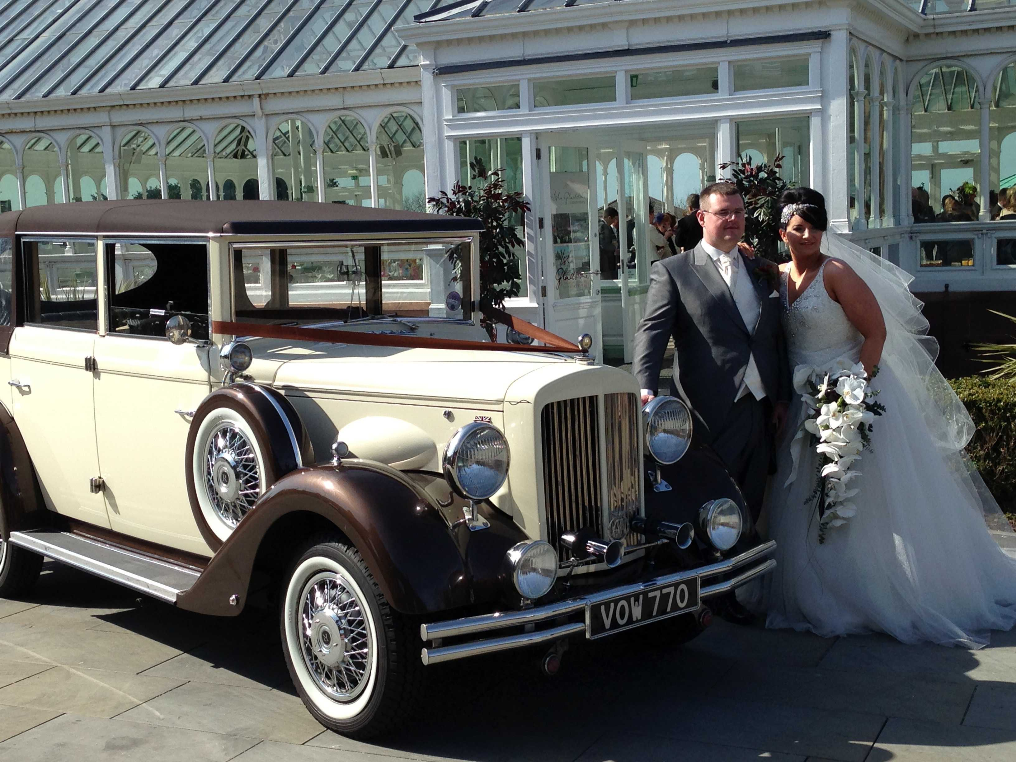 Bride and groom taking a picture with the vintage car
