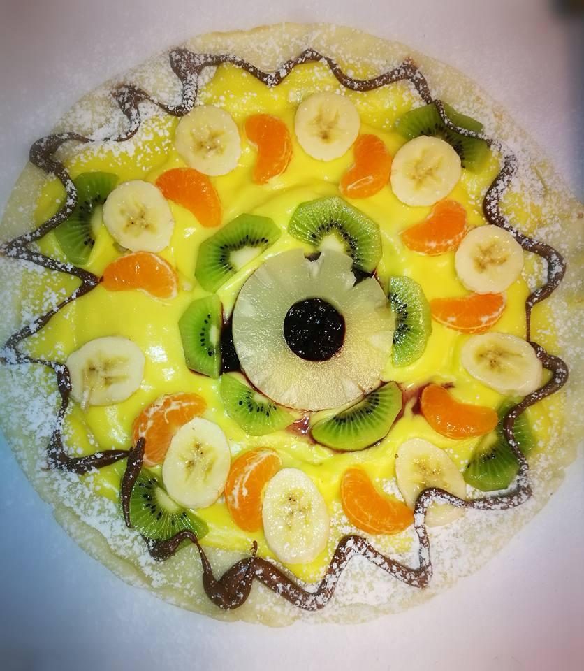 una crepe con delle fette di frutta e crema pasticcera