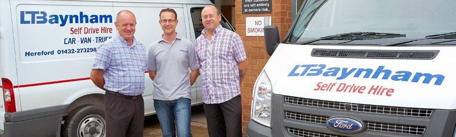 3 L T Baynham employess in front of some vehicle rental vans
