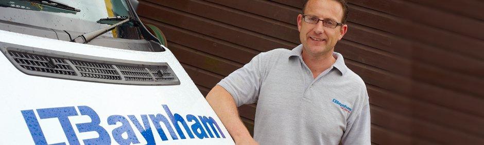 L T Baynham emplyee leaning against van